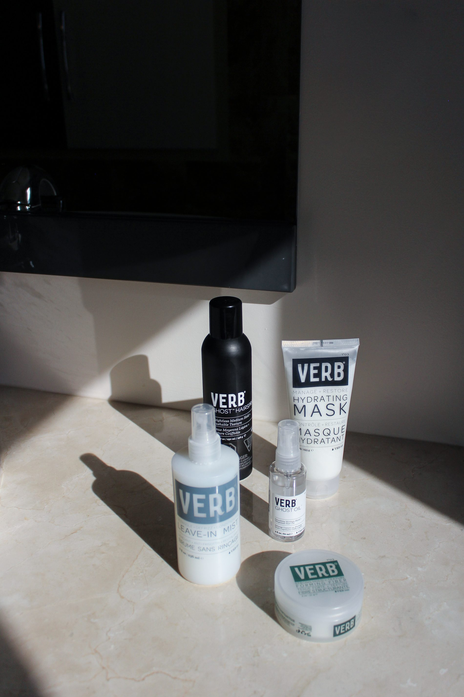 A bright light shining over a collection of hair products placed on a marble countertop