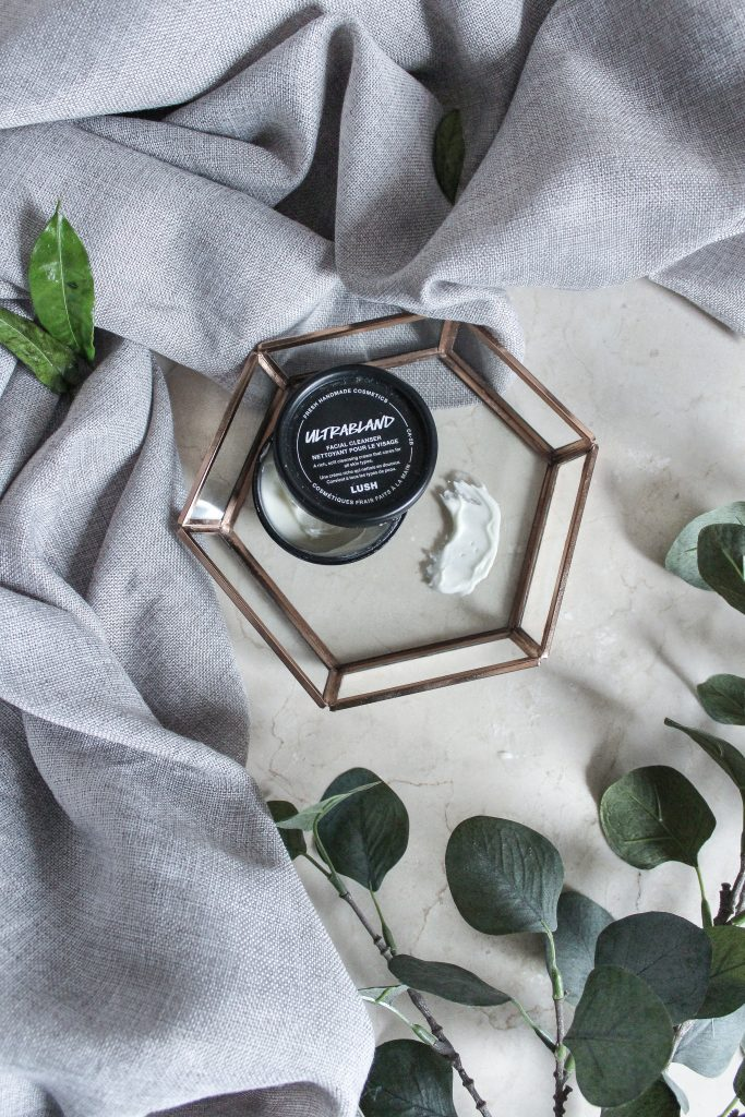 An Ultrabland pre-cleansing balm with a grey towel, green leaf branch, and jewelry tray on the bathroom countertop