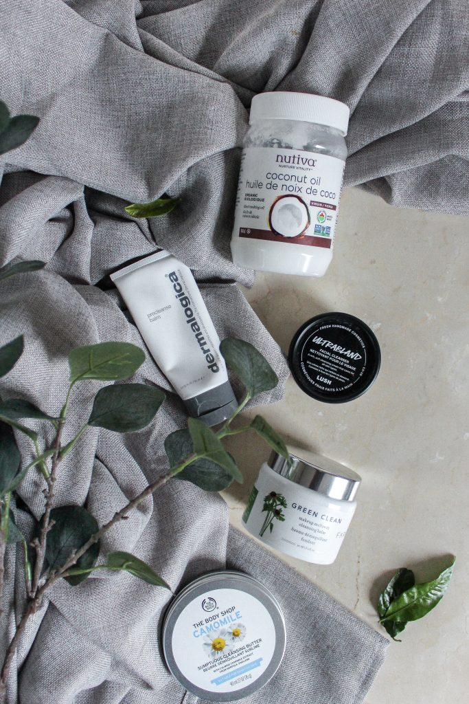 Different pre-cleansing balms placed on the bathroom countertop with a grey towel and a green branch