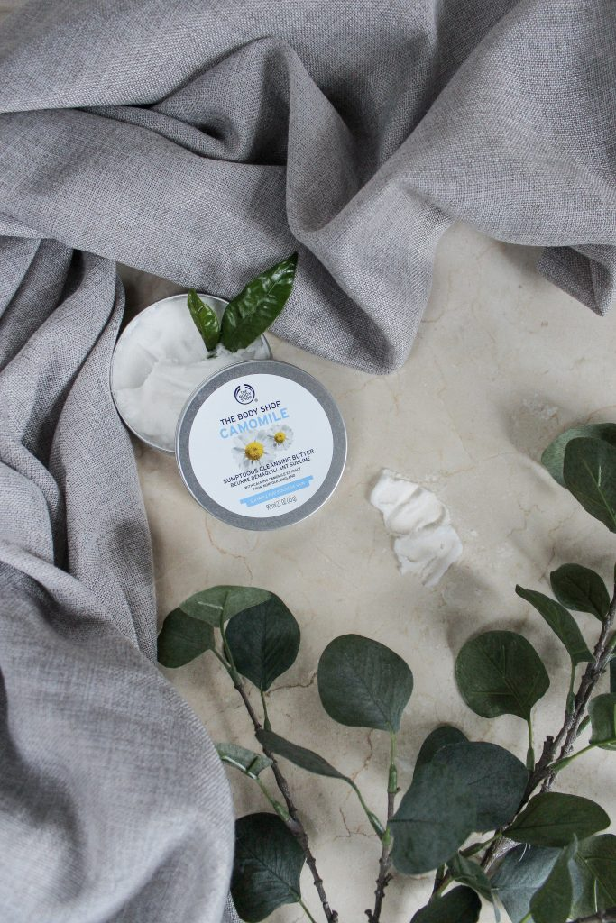 A Camomile pre-cleansing balm placed on the bathroom countertop and decorated with a green flower branch and a grey towel