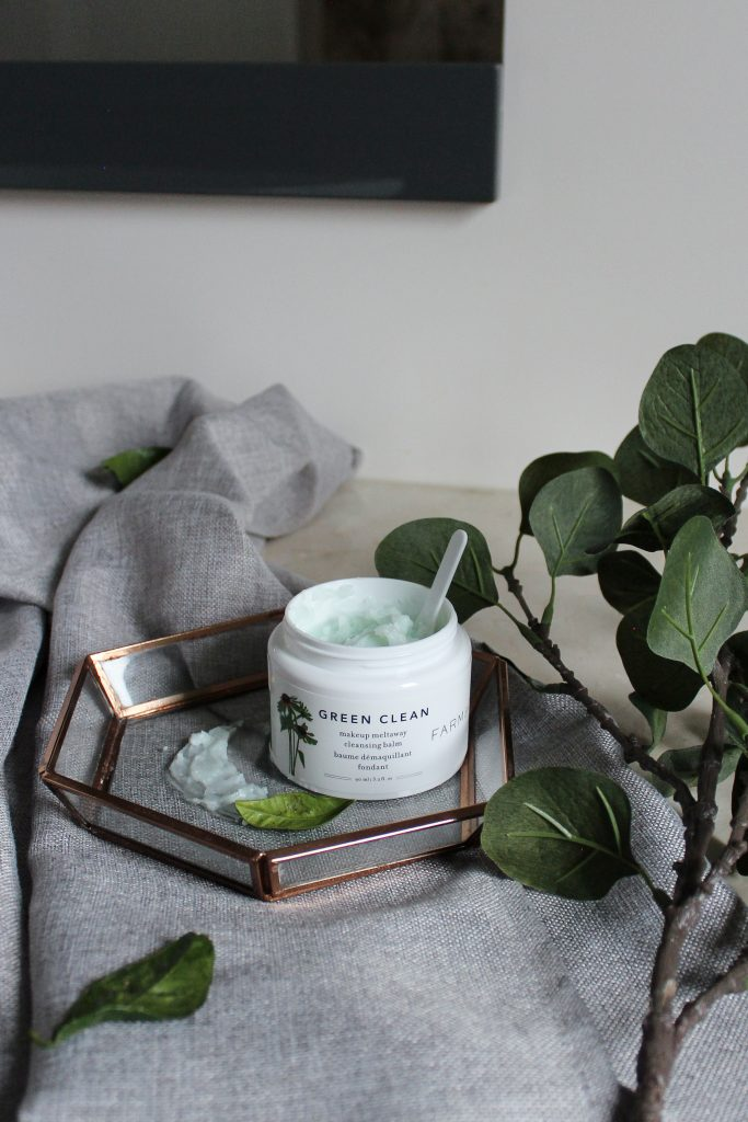 An Opened Green Clean Pre-Cleansing Balm placed on a clear jewelry tray on top of a grey towel on the bathroom countertop