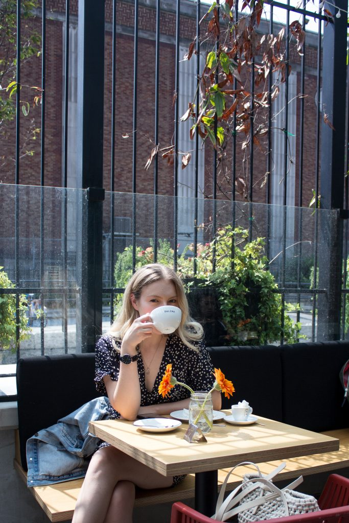 A woman sipping coffee on a patio at a cafe