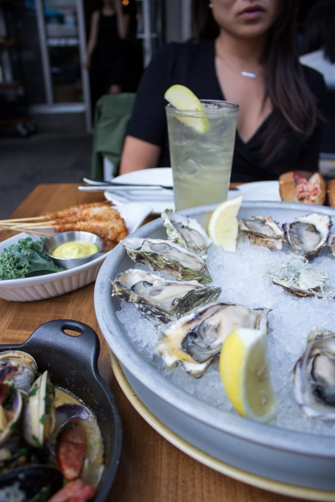 A woman sitting at a table with seafood appetizers and oysters served on a bed of ice