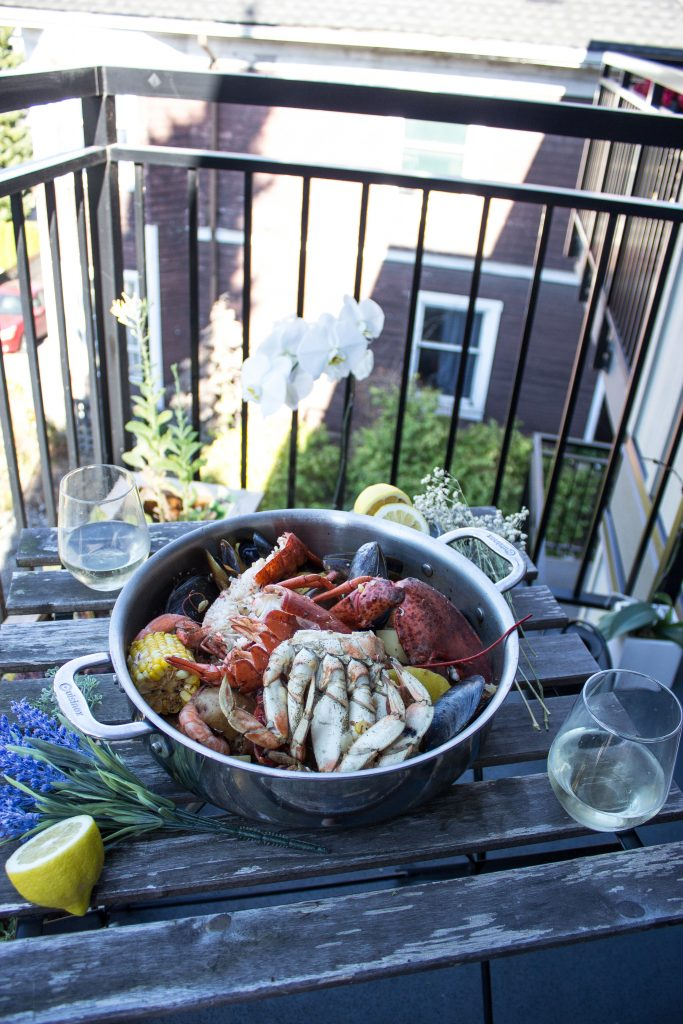 seafood boil in a pot on the table with wine and decorations