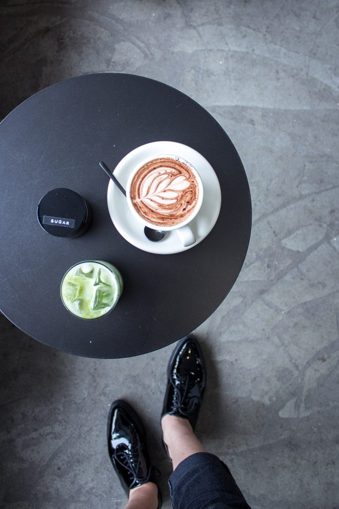 a matcha iced coffee and hot chocolate placed on a black coffee table in a cafe, with a woman's black shoes in the background