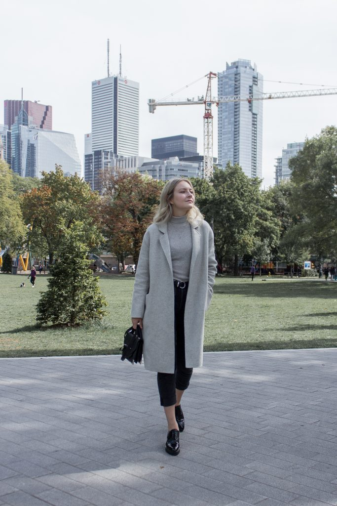 a blonde woman posing in a park while wearing a light grey sweater and coat, black jeans, and black shoes