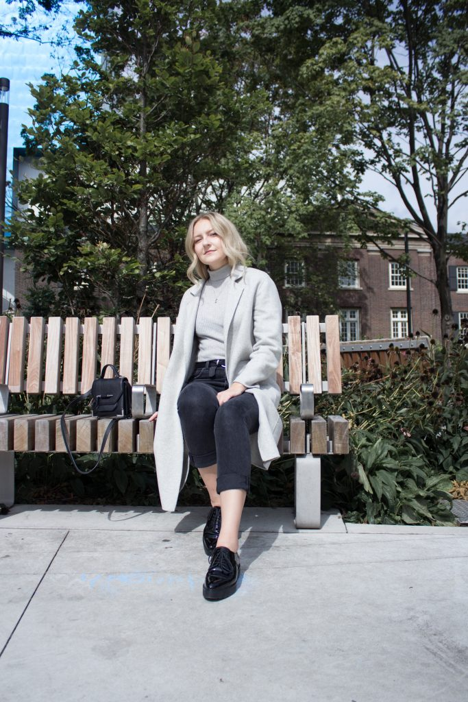 a blonde woman sitting on a park bench, wearing a grey sweater and coat, black jeans, black shoes, and black crossbody purse