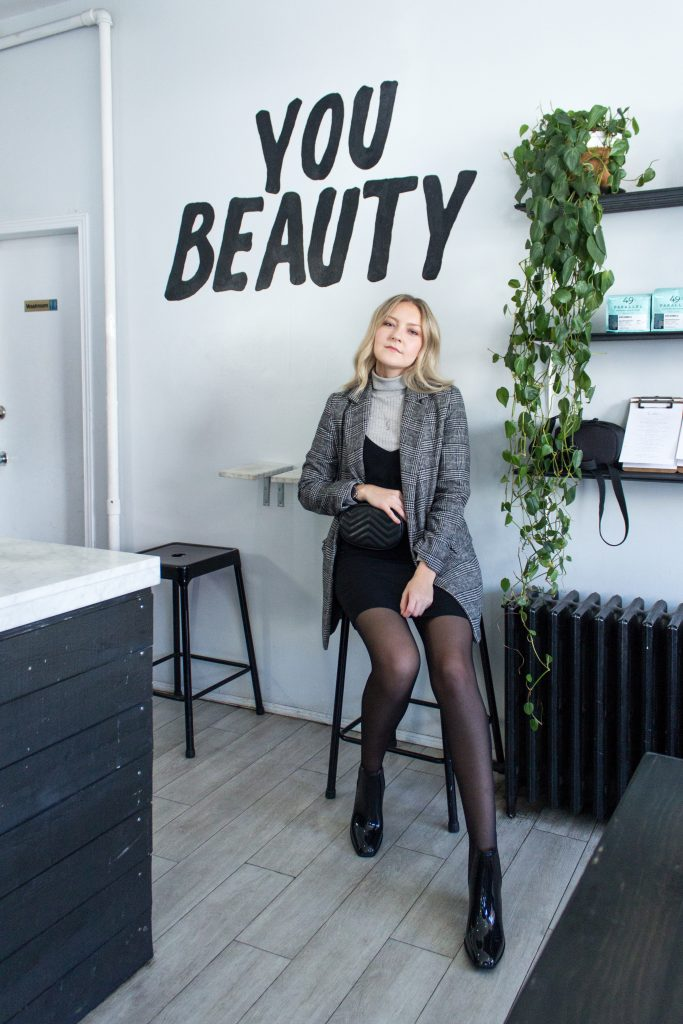 A blonde woman posing in a coffee shop wearing a grey turtleneck, a short black dress, a plaid blazer, black pantyhose, and heeled rubber boots