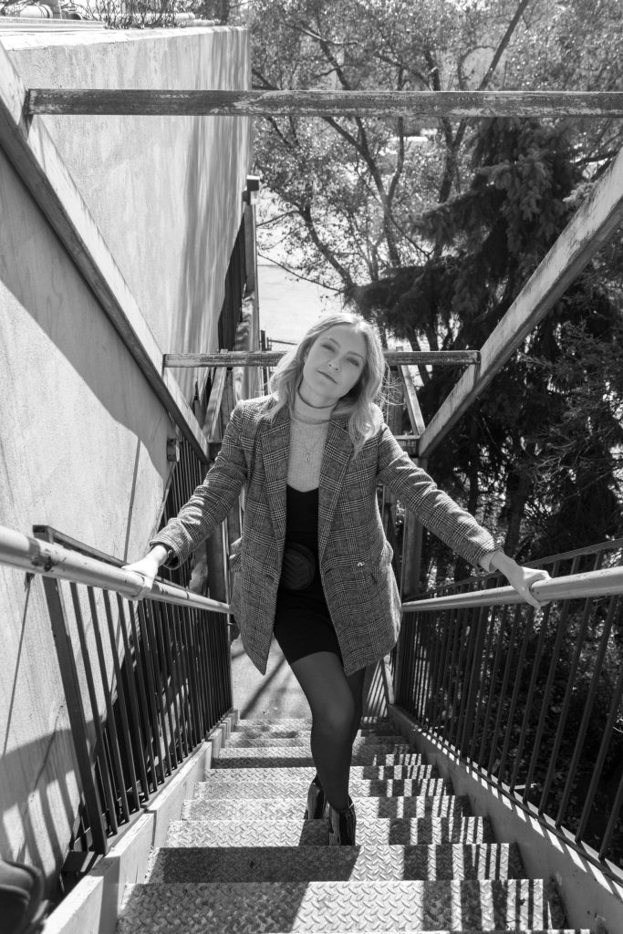 a black and white photo of a blonde woman posing on the stairs of a parking lot