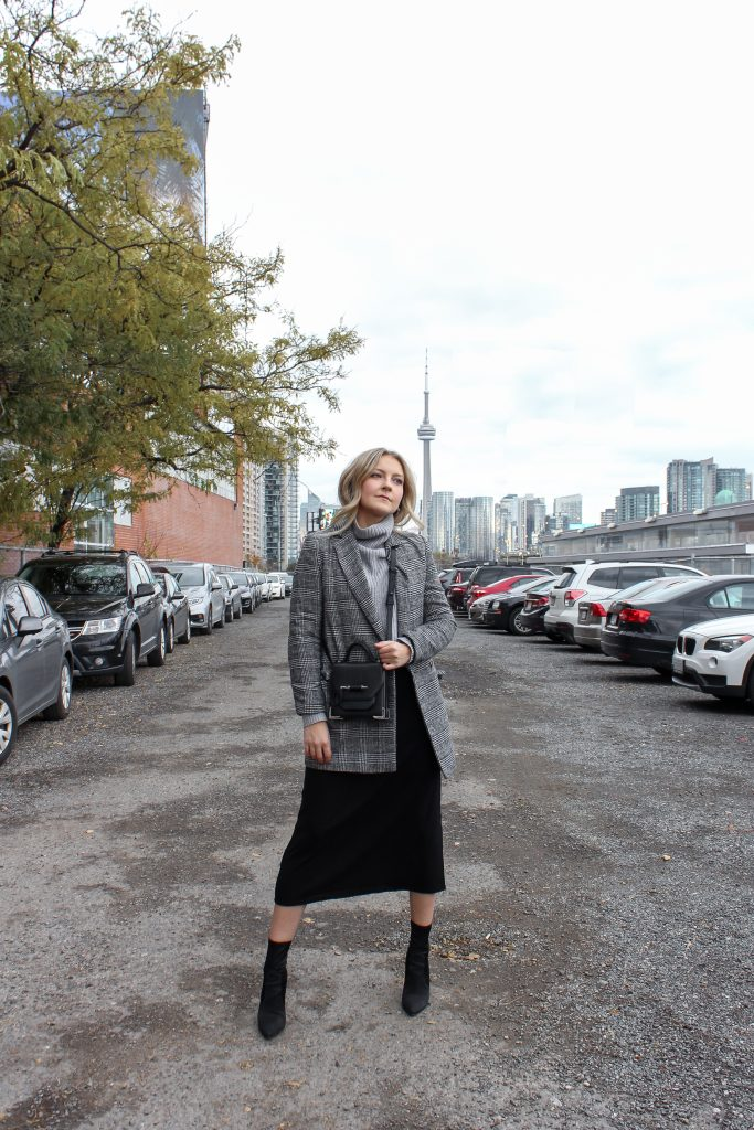 A woman in wearing a black midi skirt with a grey sweater, checkered blazer, black boots, and black purse.