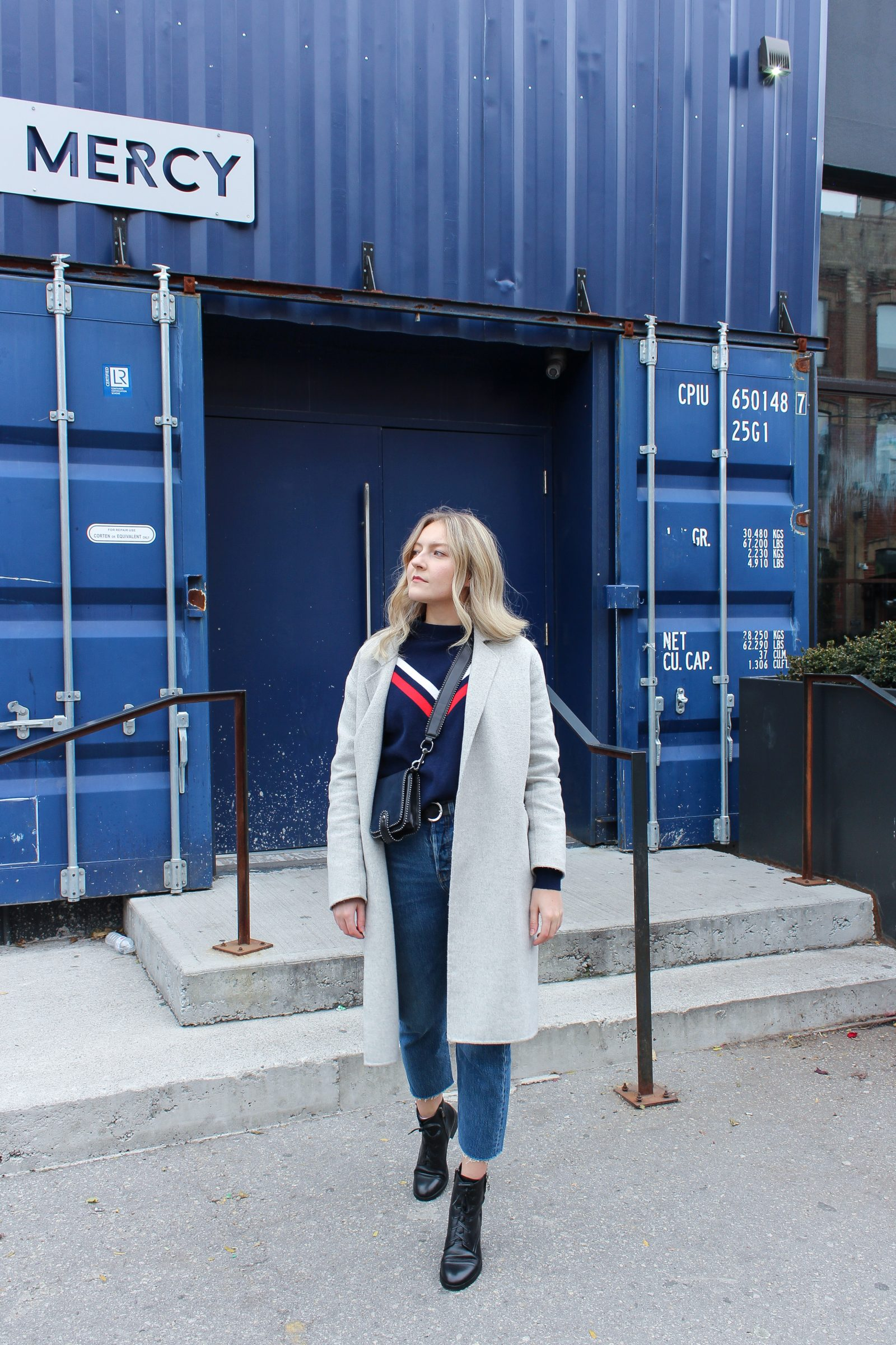 A blonde woman wearing a blue vintage sweater, crossbody bag, oversized grey coat, and black combat boots, in front of a blue shipping container