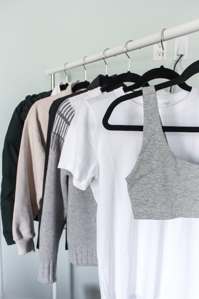 A tank bra, white t-shirt, two sweaters, and a green puffer coat hanging on a rack in a light green room