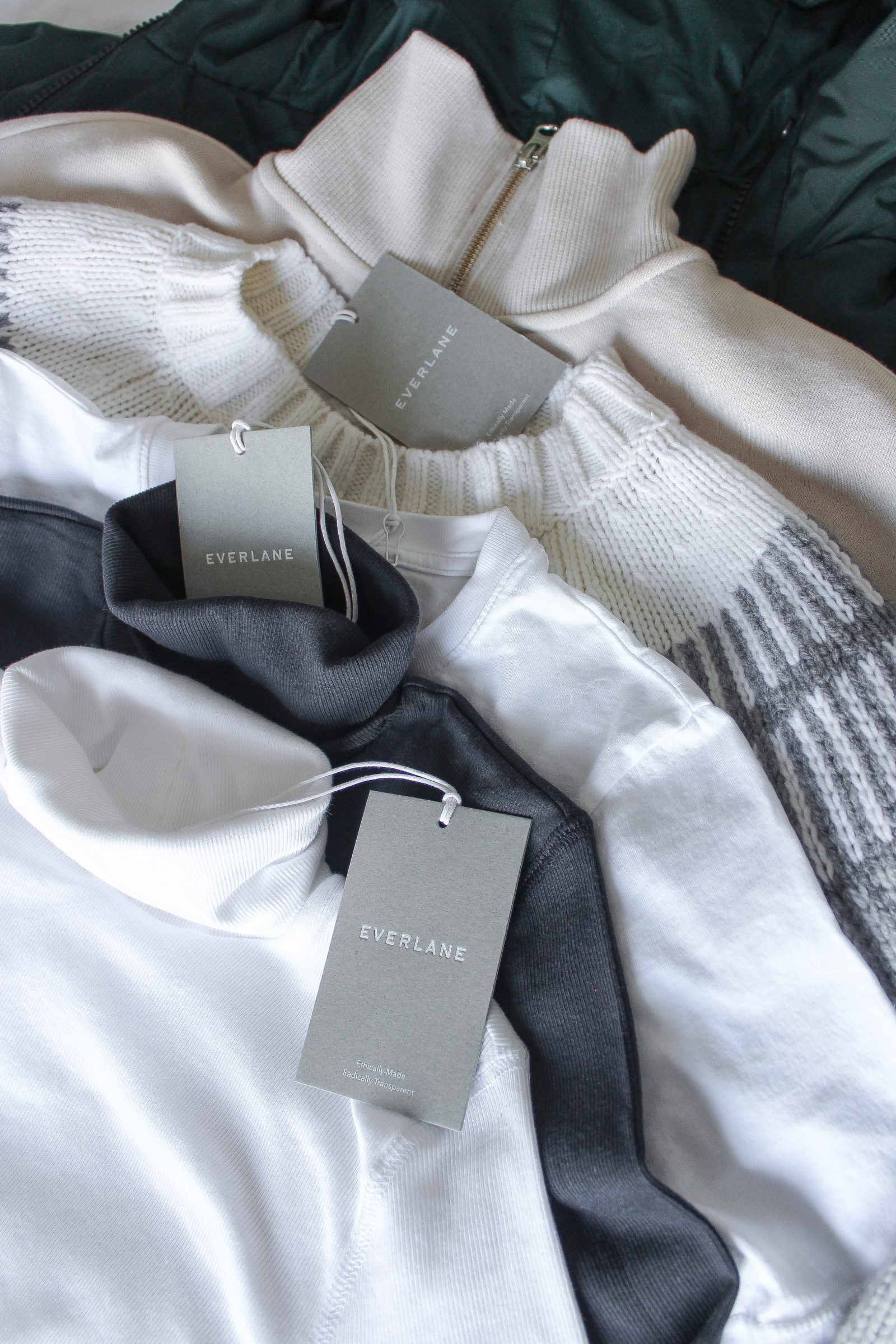 A white and black turtleneck, two sweaters, and a green coat neatly laid on top of one another on the bed, with Everlane tags made visible