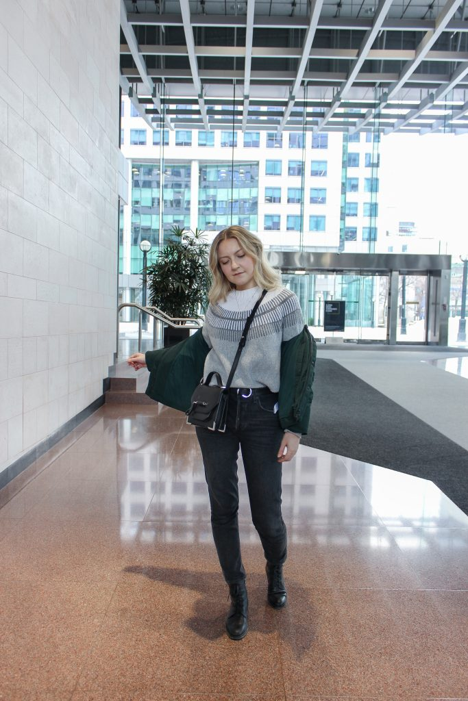 A blonde woman posing in an Everlane ski sweater, green puffer coat, black jeans, and a black crossbody bag inside an indoor building complex