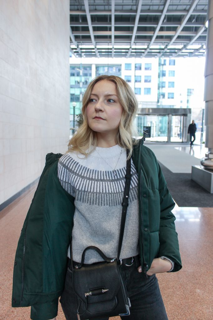 A blonde woman posing in a green short puffer coat, ski sweater, black jeans, and black crossbody inside a building complex