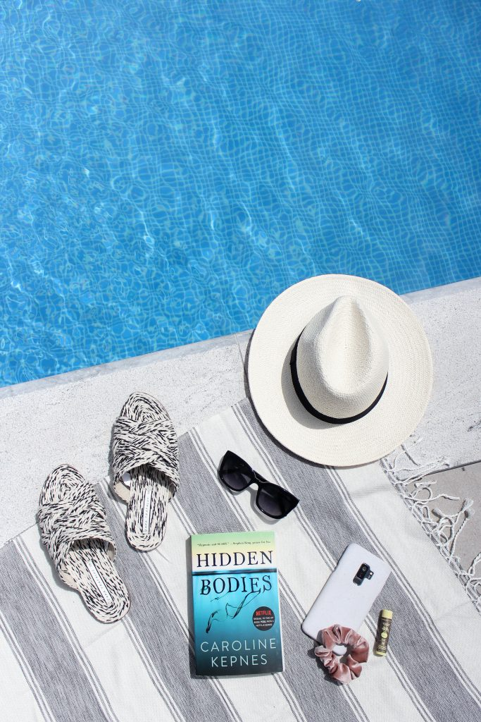 A white hat, book, phone, hair scrunchie, pool slides, sunglasses and a turkish towel on the edge of the pool