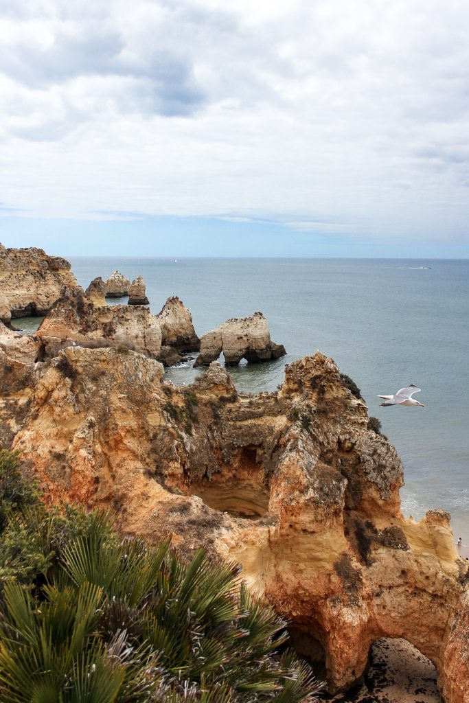 A viewpoint overlooking the blue waters and multicoloured rock formations of a beach in Lagos