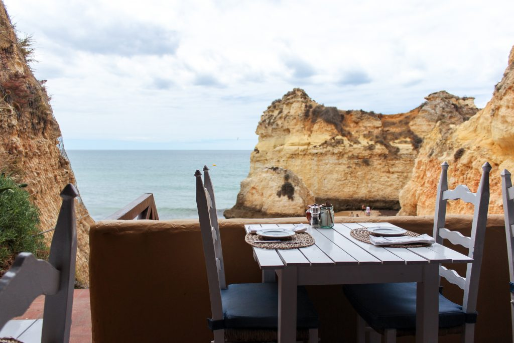 An empty table at a restaurant overlooking the beach and rocks formations in Lagos, Portugal