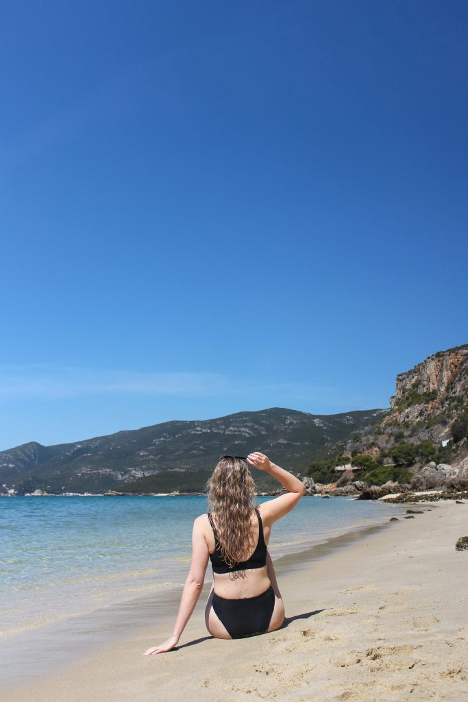 A blonde woman with her back facing the camera, looking onto green mountains in the Arrábida Natural Park