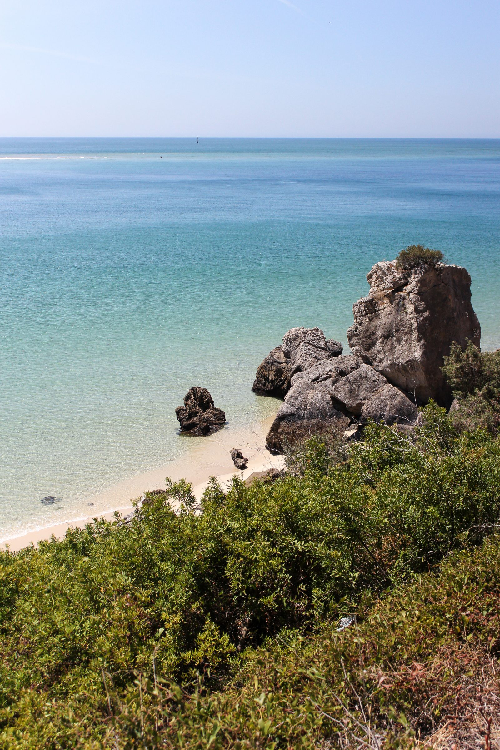 A viewpoint overlooking clear turqouise ocean water, green trees, and large rock formations in the Arrábida Natural Park