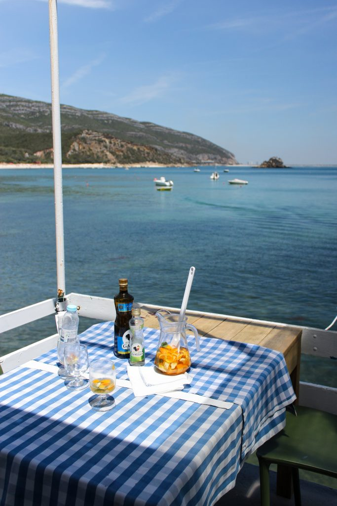A closeup of a messy table on a restaurant patio overlooking blue ocean waters and small white boats in the Arrábida Natural Park