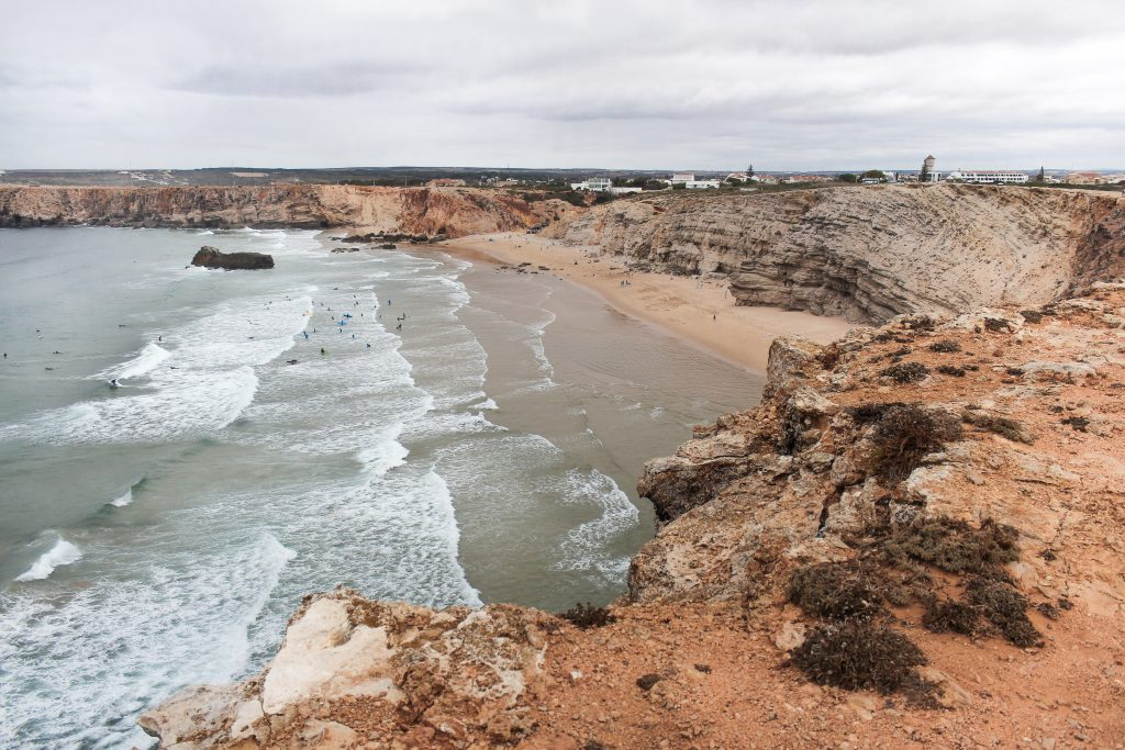 A wavy beach filled with surfers and surrounded by copper-coloured cliffs in Sagres