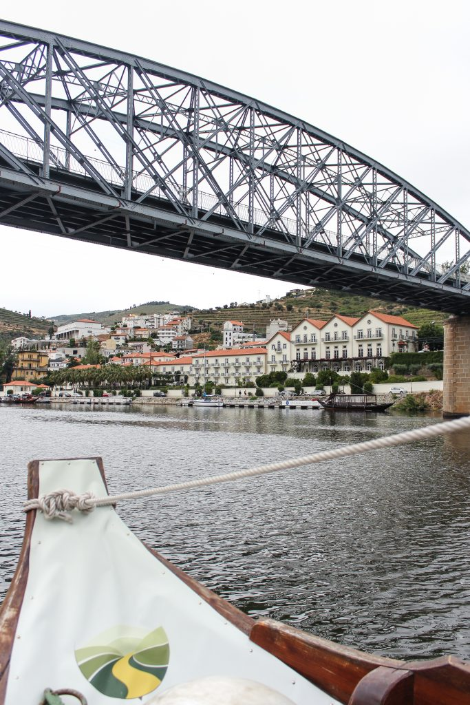 A view of a bridge and riverside hotels from a small boat in Douro Valley