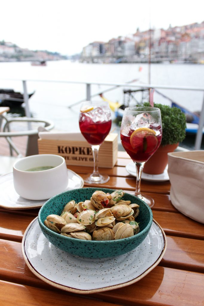 Two red sangrias and fresh clams on a table at a restaurant overlooking the Douro River in Porto