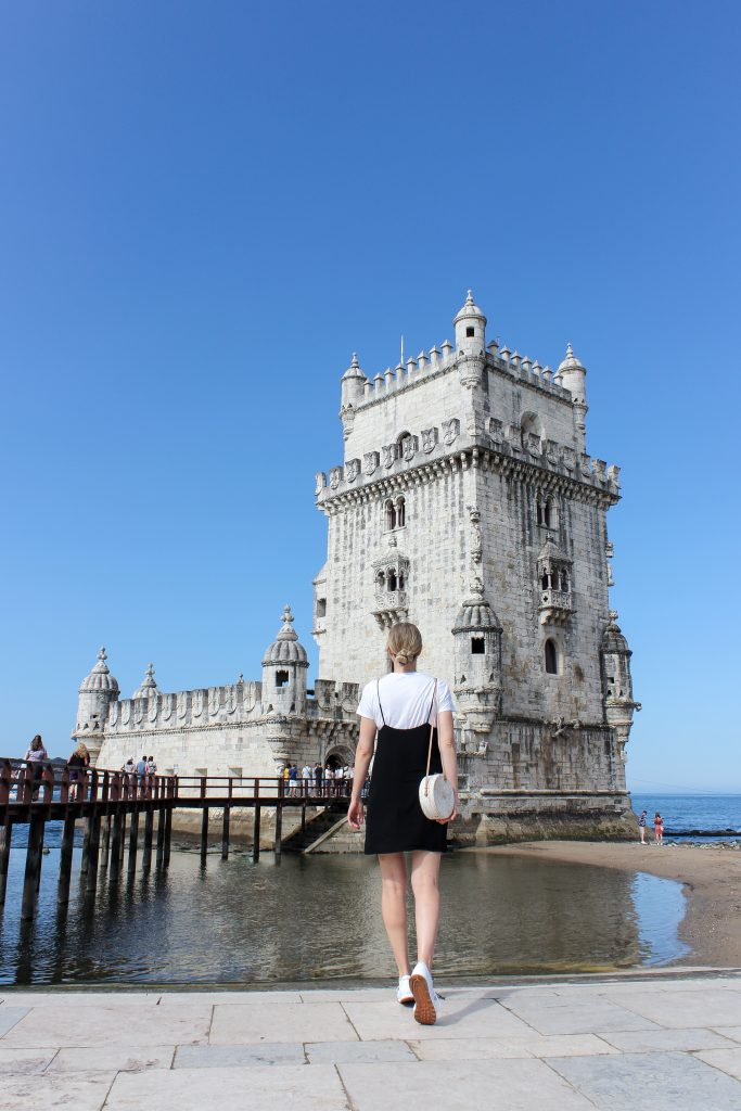 A blonde woman walking towards the Belem Tower in Lisbon