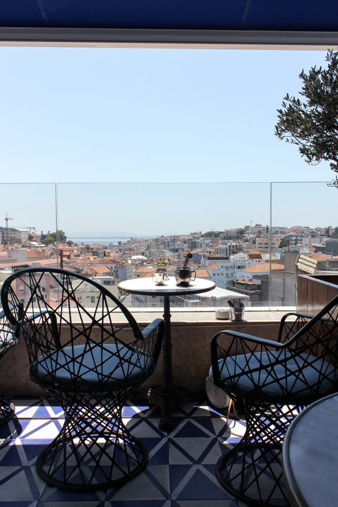 Two empty chairs and a round table with drinks on patio overlooking Lisbon