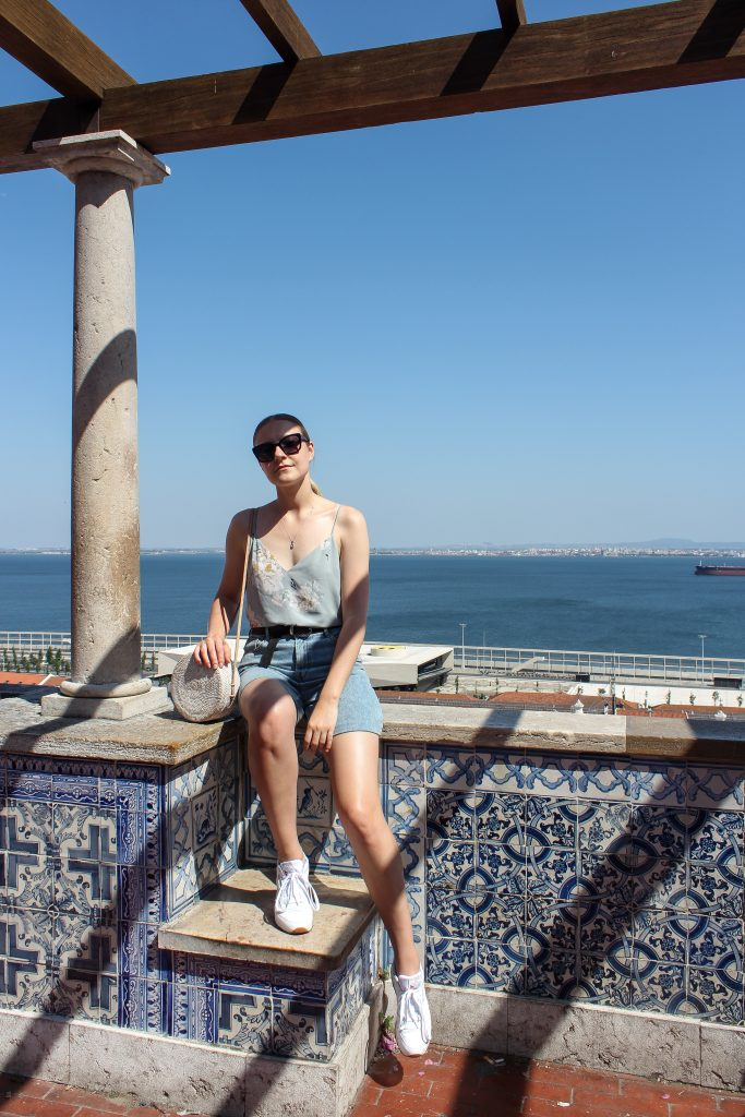A blonde woman wearing a floral tank top and jean cargo shorts posing on top of a viewpoint overlooking the water in Lisbon