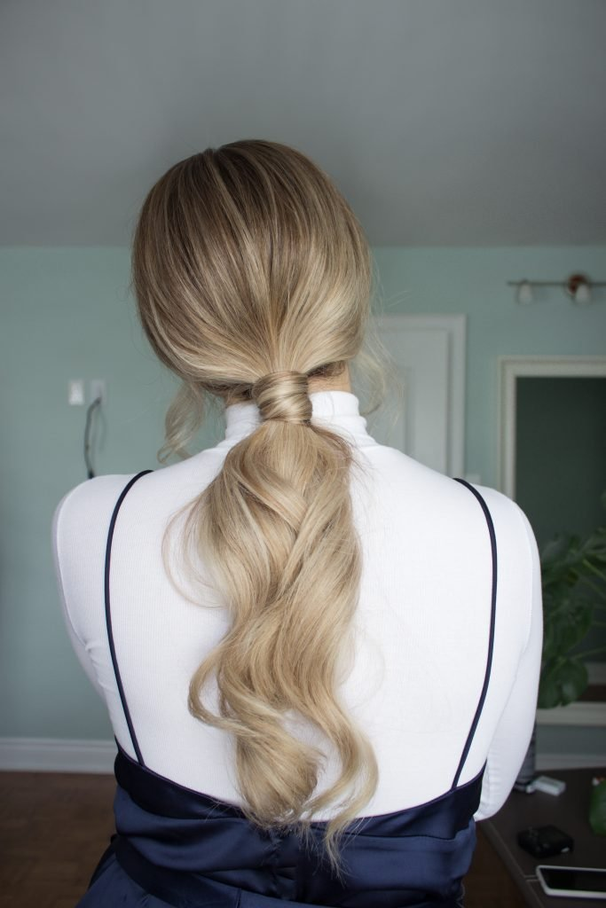 Blonde woman wearing her long, wavy hair in a loose ponytail for a Holiday Look with Verb Hair Products