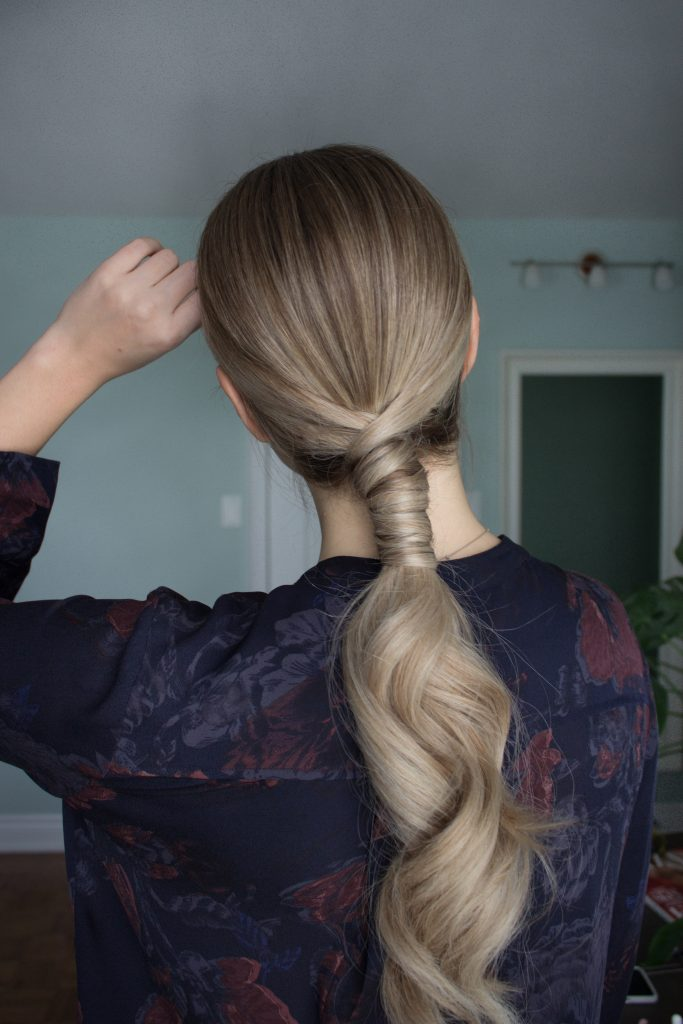 Blonde woman wearing her long, wavy hair in a sleek ponytail styled with Verb Hair Products for a Holiday Look