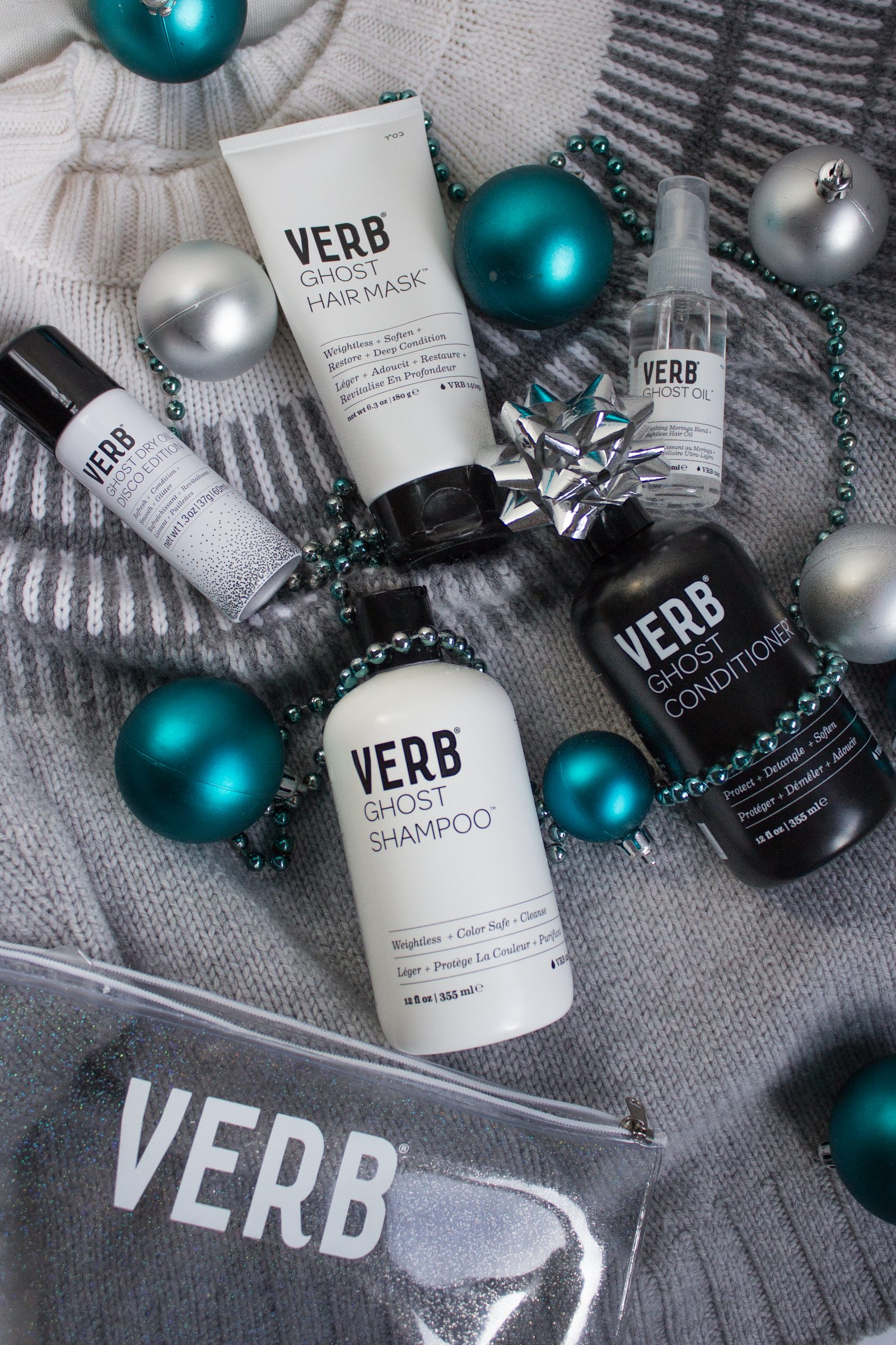 Hair products from Verb's Ghost Collection are sprawled out on a grey sweater, decorated with teal and silver ornaments