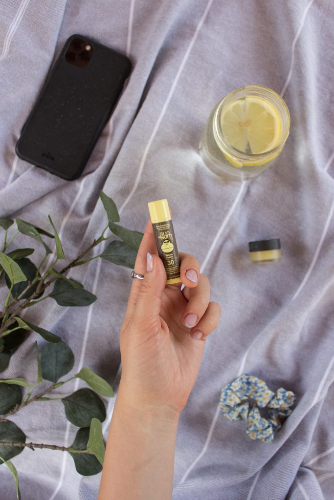 "A hand holding the ""Original SPF 30 Moisturizing Lip Balm"" by Sun Bum with a phone, lemon water, scrunchie, lip balm and leafed branches in the background"