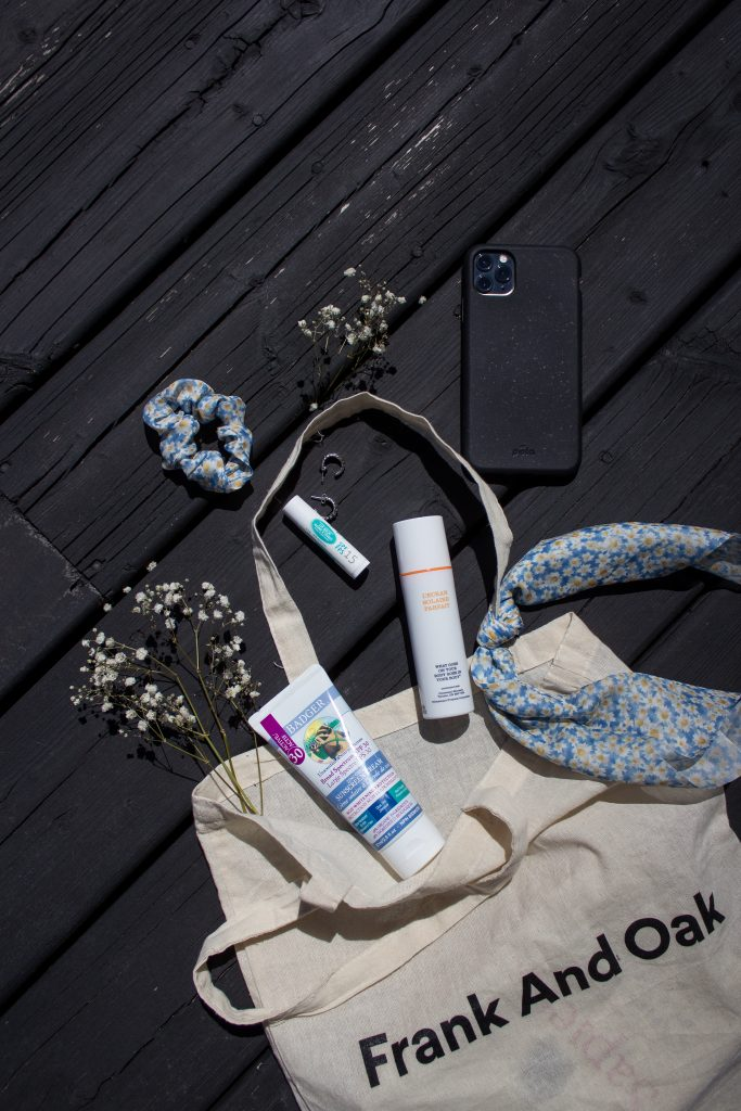 Three sunscreens pictured on a black wooden deck, peaking out of an ivory bag along with a scrunchie, earrings, small scarf, cellphone, and flowers